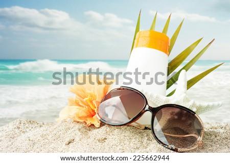 Sunglasses  on sand beach - stock photo