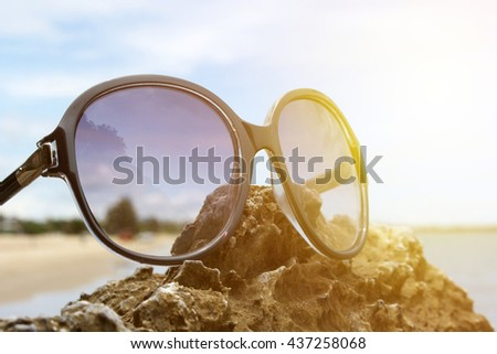 sunglasses on the rocky beach background