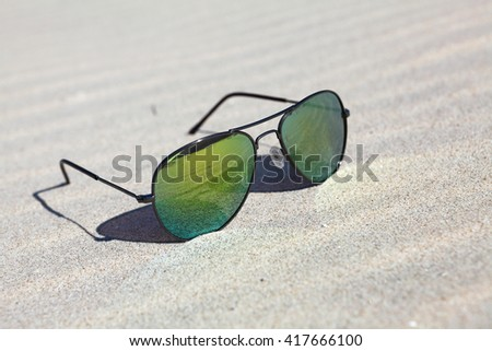 Sunglasses on the sand , reflection of beach in sunglasses - stock photo