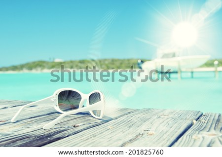 Sunglasses on the wooden jetty. Exuma, Bahamas - stock photo