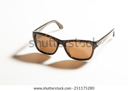sunglasses on white background with long shadow - stock photo