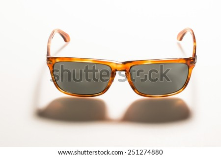 sunglasses on white background with long shadow