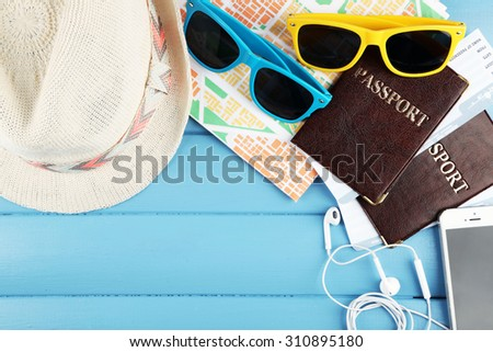 Sunglasses, passports, hats and map on color wooden background. Preparing for travel concept - stock photo