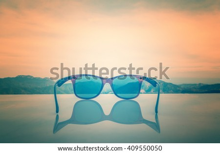 Sunglasses placed on the table with mountain View background in the evening.Image to soft blurred and made with color filters and vintage effect style pictures.