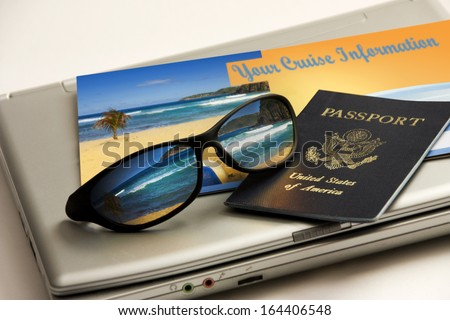 Sunglasses reflect an exotic Caribbean beach vacation with passport, cruise information and travel laptop against a white backdrop. All elements including brochure my own. - stock photo