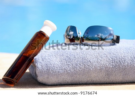 Sunglasses, towel and oil bottle by the swimming pool - stock photo