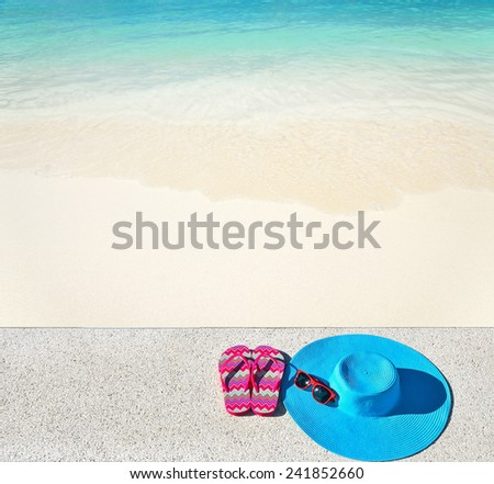Sunhat with sunglasses and flip-flops on stone platform beside beach -- Concept of vacation   - stock photo