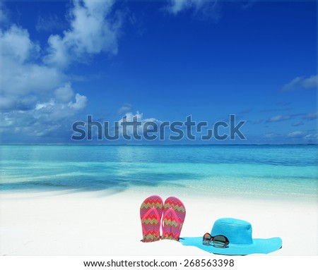 Sunhat with sunglasses and slippers at the tropical beach -- Tropical beach vacation and travel concept   - stock photo