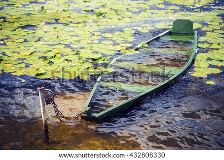 Sunk boat full of water on the lake at summer  - stock photo