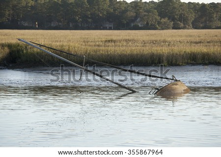 Sunken sailboat with mast out of the water - stock photo