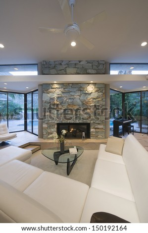 Sunken seating area and stone fireplace at modern home - stock photo
