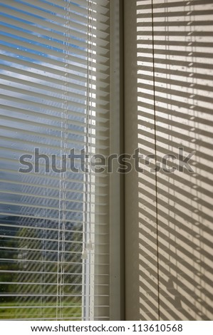 Sunlight after a storm breaks through the blinds - stock photo