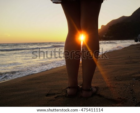 Sunlight between legs. Beautiful young woman watching the sunset at the shore