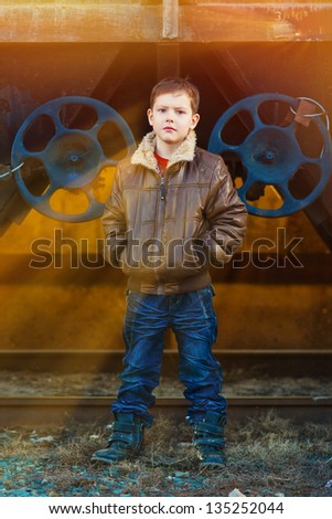 sunlight boy blonde tramp in a brown jacket, crumpled jeans on the street near the railway wagons - stock photo