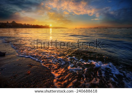 Sunlight breaking at dawn over a sandy shore - stock photo
