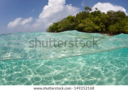Sunlight dances across bright white sand in the Solomon Islands.  This area is found within the Coral Triangle and is high biological diversity. - stock photo