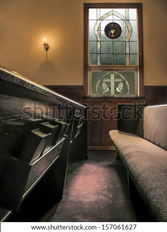 sunlight falls across pews in a small church from stained glass window and light of small wall