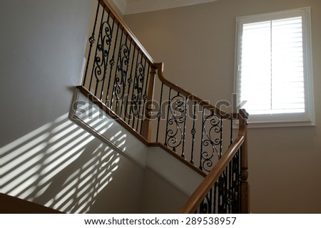 Sunlight from an open window with blinds shines onto stairway creating diagonal lines on wall.