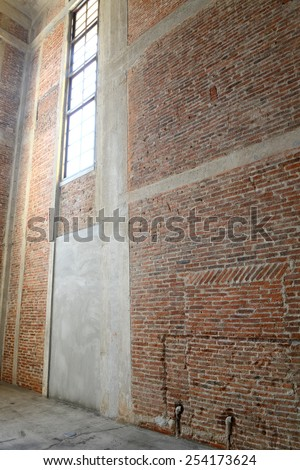 Sunlight from window on the brick walls inside of old building - stock photo