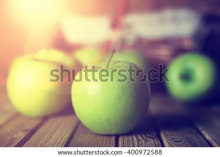 sunlight green apple in a basket wooden background - stock photo