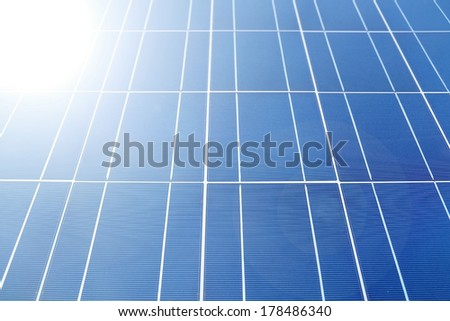 Sunlight hitting solar panels or photovoltaics to generate solar energy. Selective focus. - stock photo