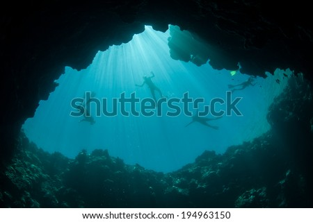 Sunlight illuminates the top of a submerged sink hole on the edge of Palau's barrier reef. The dim shadows of underwater caves and caverns provide habitat for many marine species. - stock photo