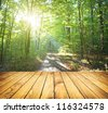 Sunlight in thesummer forest with wood planks floor - stock photo
