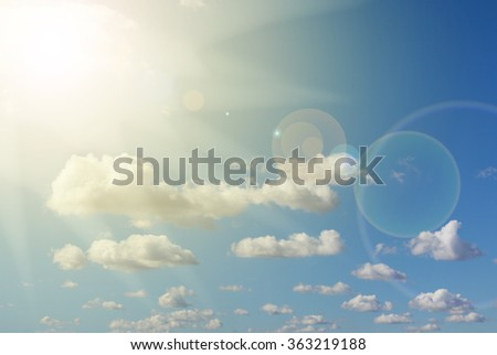 sunlight, lens flare , blue sky and clouds - stock photo