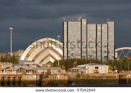 Sunlight on buildings as storm clouds gather beside River Clyde in Glasgow, Scotland, UK, Europe - stock photo