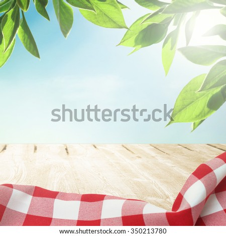 Sunlight on summer sky with wooden picnic table - stock photo