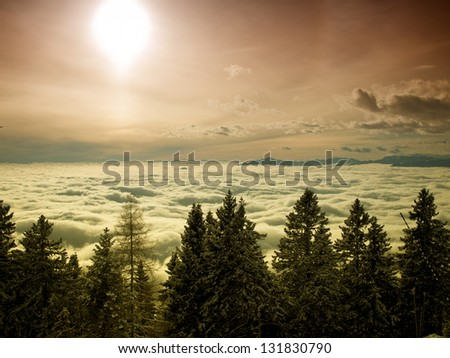 Sunlight over the foggy valley during winter. - stock photo