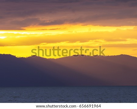 Sunlight rays in an orange sky streak over a ridge on Ko Chang, east Thailand