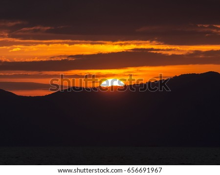 Sunlight rays in an orange sky streaks over a ridge on Ko Chang, east Thailand
