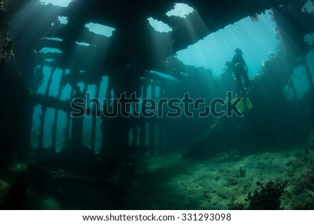 Sunlight shines down into the interior of a world war II shipwreck off the coast of Guadalcanal in the Solomon Islands. Shipwrecks act as artificial reefs, attracting many fish and invertebrates. - stock photo