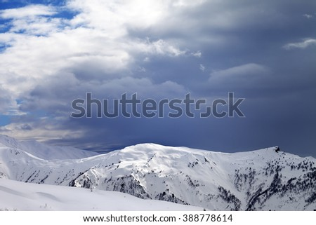 Sunlight slope and cloudy gray sky in evening. Caucasus Mountains, Svaneti region of Georgia. - stock photo