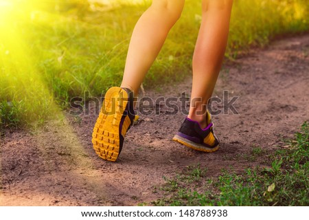 sunlight sports a shoes female large legs running, exercising and walking, fitness, running in forest - stock photo