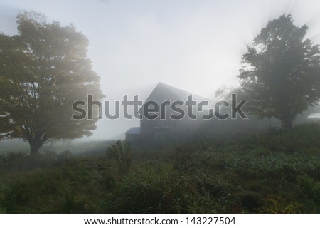 Sunlight streaking through the fog with a barn and trees on an autumn morning in Stowe, Vermont, USA - stock photo