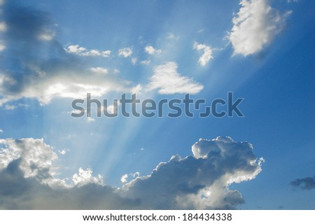 Sunlight streaming from behind a cloud - stock photo
