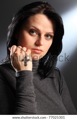 Sunlight streams into room as beautiful young caucasian woman with bright green eyes has a peaceful moment, while holding a crucifix necklace in her hand. - stock photo