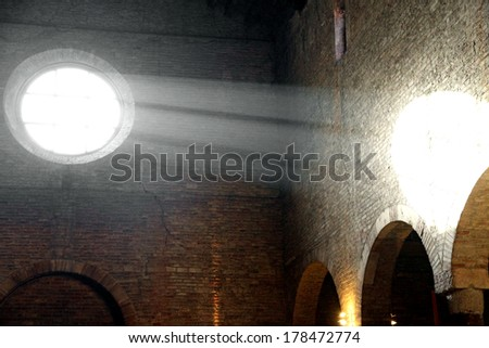 sunlight that enters from the ancient Christian Church rose window and illuminates the ancient brick wall - stock photo