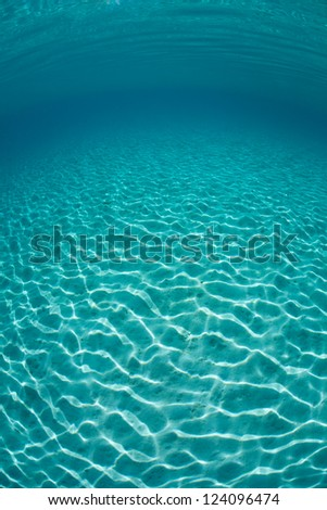 Sunlight travels in waves over a shallow stretch of white sand as it passes through clear, blue sea water in the Solomon Islands. - stock photo