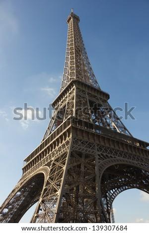 sunlit Eiffel Tower at sunset, Paris, against blue sky - stock photo