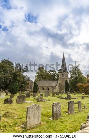 Sunlit picturesque church  and graveyard, Lower Slaughter, Gloucestershire,UK - stock photo