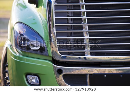 Sunlit powerful modern stylish and comfortable green big rig semi truck of latest model commercial long-distance transport shiny chrome grille efficient headlight in parking lot waiting for cargo. - stock photo