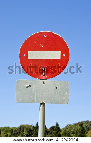 Sunlit red stop sign against blue sky - stock photo