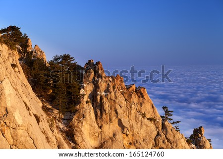 Sunlit rocks and sea in clouds at evening. Crimean mountains in winter, Ukraine. - stock photo