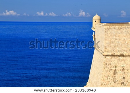 Sunlit stone walls above blue Adriatic sea, Dubrovnik, Croatia - stock photo