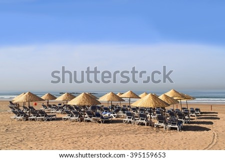 Sunlounger and sunshade on the beach waiting for bather