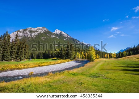 Sunny autumn day in the Canadian Rockies. Dry creek in a mountain valley Banff park - stock photo