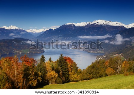 Sunny autumn morning view on Lake Millstatt in Austria, Carinthia. With golden, orange and red trees, small towns and villages on shores and snow-capped mountains in the background. - stock photo